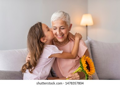 Cute girl giving a bunch of flowers to her grandmother. Happy senior grandma hugging granddaughter thanking for gift and flowers. Girl kissing giving flowers bouquet congratulating smiling old grandma