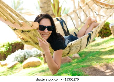 cute girl with glasses resting on a hammock