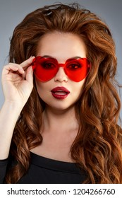 Cute girl with glasses in the shape of a heart. Funny, positive, funny model in red sunglasses.