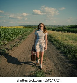 Cute girl goes on a dirt road in field with a suitcase in hand