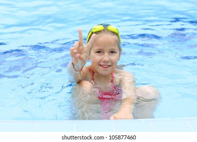 Cute girl with goggles in swimming pool showing victory sign