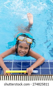 Cute girl with goggles in swimming pool