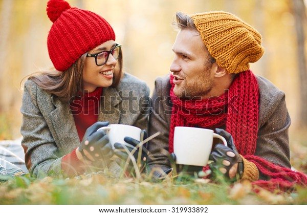 Cute girl and guy with tea or coffee talking in natural environment