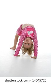 cute girl in a gymnastics bridge position and a pink cheering outfit