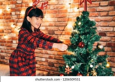 cute girl hanging ornaments on the christmas tree in the living room. xmas tree start being colorful in December. prepare to celebrate Christmas at home concept.