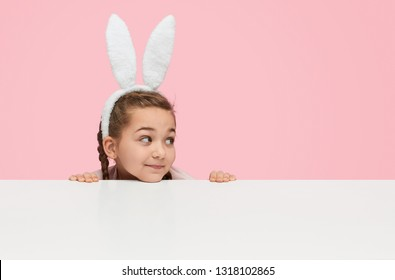 Cute girl in headband with white fluffy ears looking curiously away being behind white table on pink background