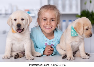 Cute girl with her adorable labrador puppy dogs at the veterinary - group portrait with a broad smile