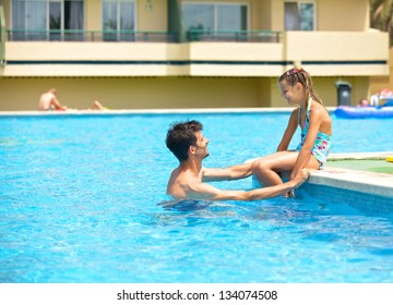 Cute girl with her father playing in a pool of water during the summer