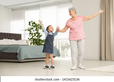 Cute girl and her grandmother dancing at home