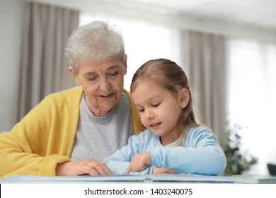 Cute girl and her grandmother reading book at home