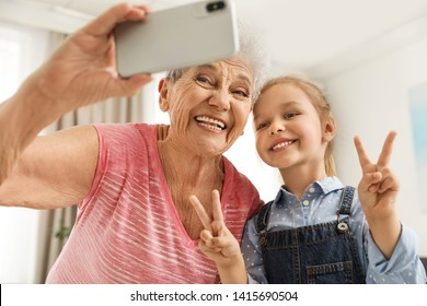 Cute girl and her grandmother taking selfie  at home