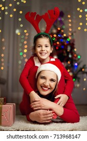 Cute girl and her mother on a Christmas/New Year's Eve, having fun