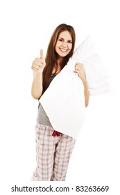 Cute girl in her pajamas holding a pillow, showing thumb up.  Isolated on white background