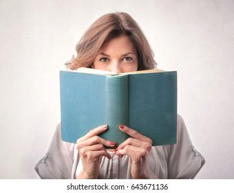 Cute girl hiding behind a book