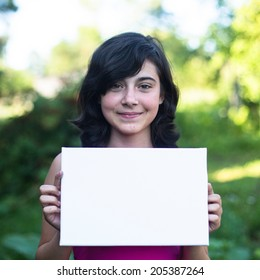 Cute girl holding clean white sheet paper, outdoors (banner for your message)