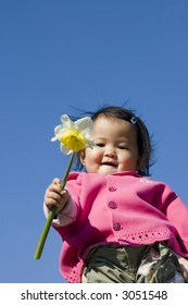 cute girl holding a daffodil (narcissus) flower.