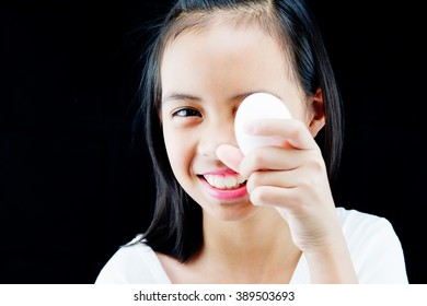 Cute girl holding duck egg isolated on black background, Nice eye and smile, She prepare to paint the Easter