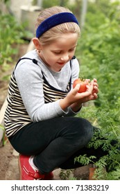 Cute girl holding the first tomato from the harvest