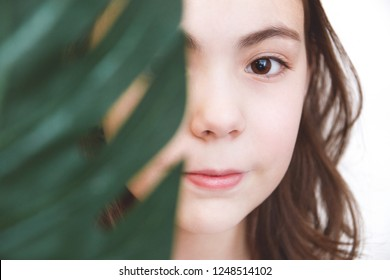 cute girl holding a green leaf of monstera, covering half her face on white background