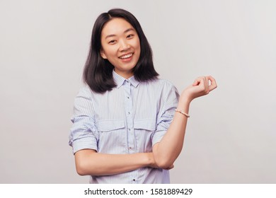 Cute girl holding hand on stomach and raises arm up and flexes wrist. Charming sweet snow white smile with teeth. Businesslike beautiful young woman of Asian appearance dressed in striped office shirt