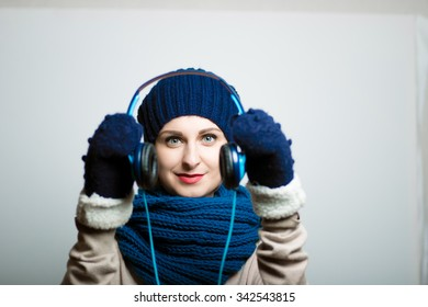 cute girl holding headphones, dressed in winter clothes, bright lifestyle photo, isolated on a gray background