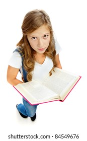 Cute girl holding open book and looking at camera in isolation