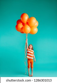 Cute girl holding orange balloons on blue background. Full length of girl child with bunch of helium balloons.