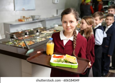Cute girl holding tray with delicious food in school cafeteria