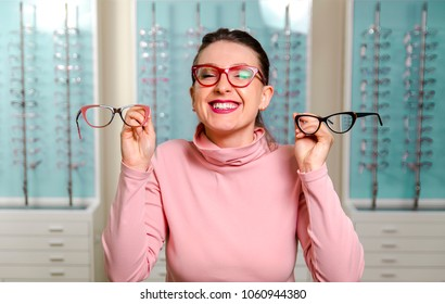Cute girl holding two eyeglasses in hands and smiling in optic store