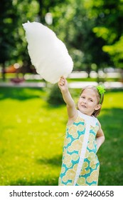 Cute girl with holding a wad of cotton candy