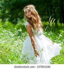 Cute girl holding white dress in green field.