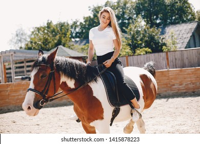 Cute girl with a horse. Lady in a white t-shirt. Woman in a summer park