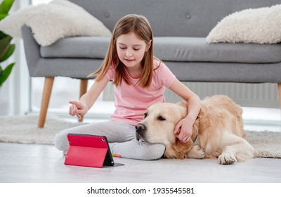 Cute girl hugging golden retriever dog and talking online with family friends on tablet