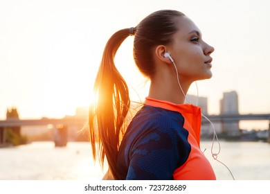 cute girl jogging staring into the distance at sunset