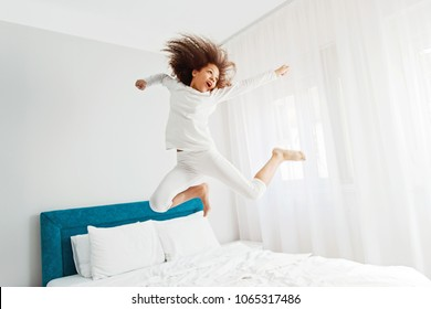 Cute girl jumping on the bed, happiness, joyful