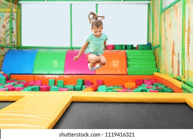 Cute girl jumping on trampoline in entertainment center