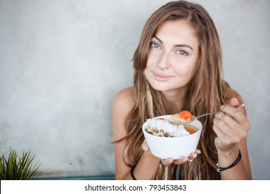 Cute girl is keeping in hands a bowl of raw vegan breakfast and a spoon