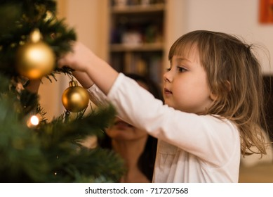 Cute girl kid decorating christmas tree with bauble