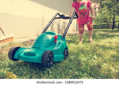 Cute girl lawn mowing with plastic toy mower.