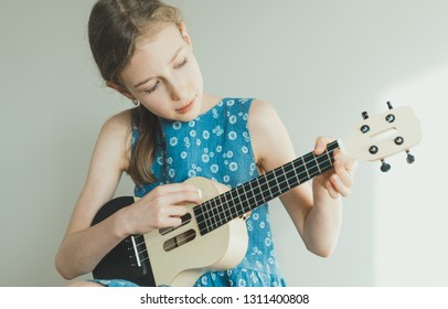 Cute girl learning to play ukulele at home.