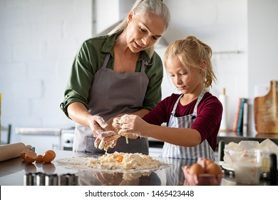 Cute girl learning preparing dough with mature grandmother in kitchen. Lovely old grandma and granddaughter preparing cookies with flour and eggs on kitchen counter. Senior granny in apron.