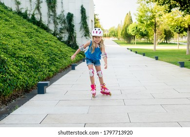 Cute girl learning  to ride rollerblades on public park on sunny day. Children playing outside. Active healthy leisure and outdoor sport for kids