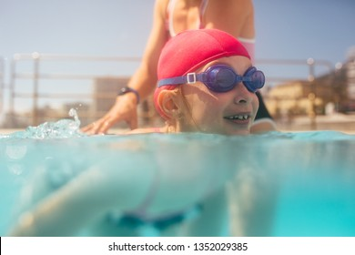 Cute girl learning to swim with coach at the leisure center. Girl having swimming lesson in the swimming pool with the coach.