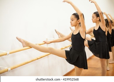Cute girl in a leotard and skirt lifting her leg and arm during a ballet dance class