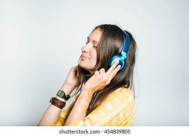 cute girl listening to music or calls with headphones, studio isolated