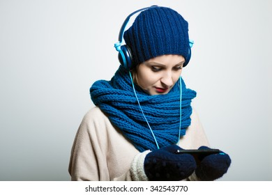 cute girl listening to music with headphones in the winter, dressed in winter clothes, bright lifestyle photo, isolated on a gray background