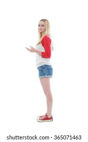 cute girl with long blonde hair wearing casual shirt, shorts and sneakers. standing against a isolated white background.
