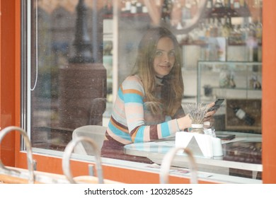 Cute girl with long hair sitting in caffe and chatting on mobile phone. Photo taken from outside, with a see through the window.