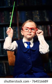 Cute girl looking like a strict teacher in the library raised her pointer to draw attention. Educational concept.