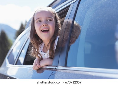 Cute girl looking out of the car window on a sunny day
